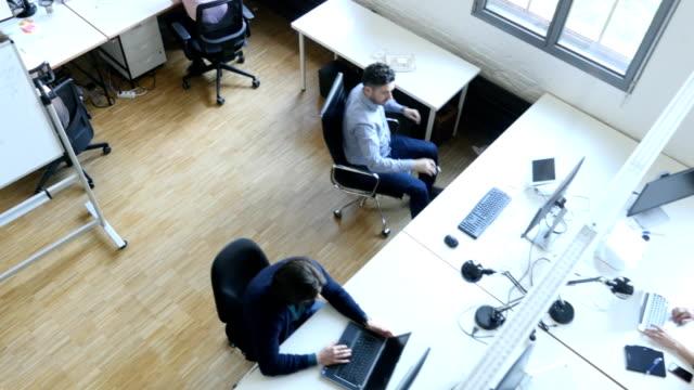 erhöhte ansicht von programmierern arbeiten am schreibtisch - stuhl stock-videos und b-roll-filmmaterial
