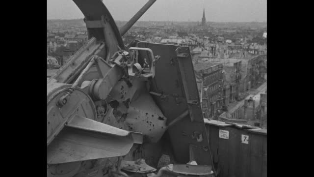 stockvideo's en b-roll-footage met a high angle view of ravaged buildings and an abandoned artillery gun at roof level pan vs the ravaged city and a street with a single vehicle moving... - puin