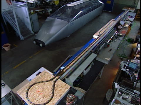 high angle view of remote-control model trains and cybertran 1 prototype in lab / pan engineers working in lab - プロトタイプ点の映像素材/bロール