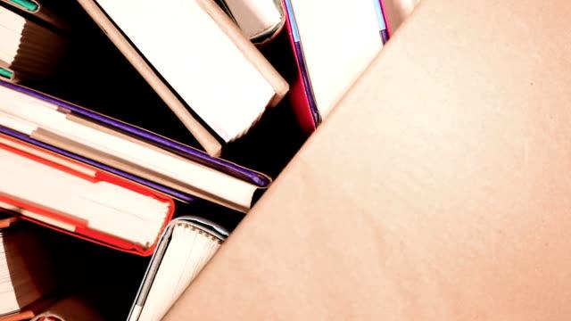 vídeos de stock e filmes b-roll de high angle view of revolving hardback books.  library or school. - capa de livro