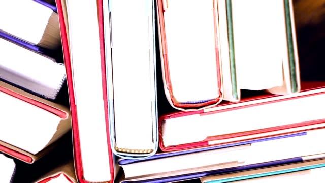 vidéos et rushes de vue grand angle de rotation des livres cartonnés.  école ou bibliothèque. - couverture de livre