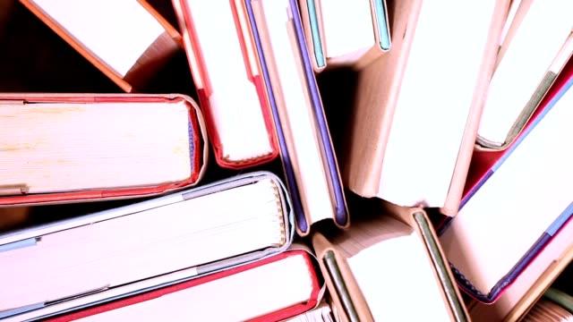 erhöhte ansicht revolvierender gebundene bücher.  bibliothek oder in der schule. - buchdeckel stock-videos und b-roll-filmmaterial