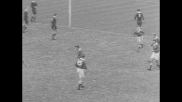 vídeos de stock e filmes b-roll de high angle view of rugby players in game / cut to royal navy cadets in stands / player kicks ball and scores / scoreboard / players on the field /... - etapa desportiva