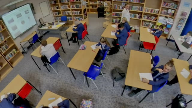 high angle view of school children of key workers at school during coronavirus lockdown observing social distancing in the classroom - angle stock videos & royalty-free footage