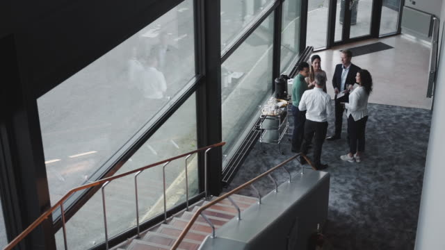high angle view of smiling business professionals standing while discussing by staircase in corridor at office - medarbetarengagemang bildbanksvideor och videomaterial från bakom kulisserna