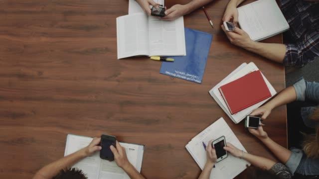 vídeos de stock, filmes e b-roll de vista de alto ângulo de estudantes em telefones em um círculo - aluno mais velho