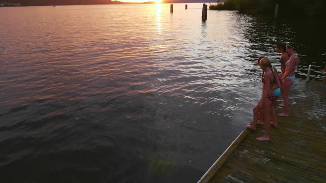 high angle view of teenagers jumping from dock into lake at sunset - only teenage girls stock videos & royalty-free footage