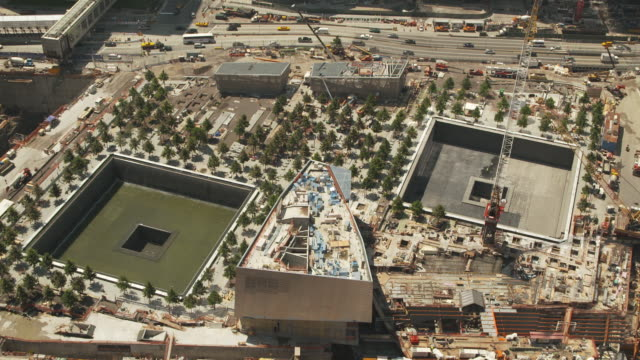 high angle view of the north and south pools of 'reflecting absence', the national september 11 memorial, in the footprints of the twin towers of the world trade center whilst under construction, summer 2011, manhattan, new york, usa. - world trade center manhattan video stock e b–roll