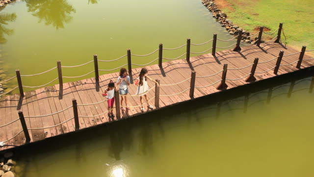 High angle view of three girls standing on a footbridge in a garden