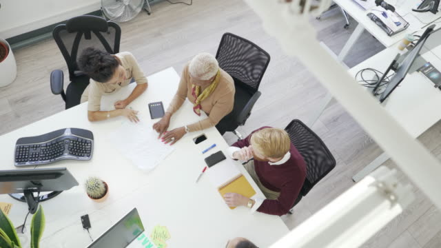 stockvideo's en b-roll-footage met a high angle view of three people in a meeting sitting around a desk. - buiten de vs