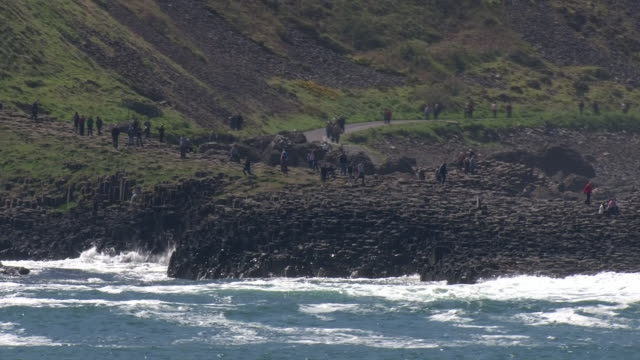 high angle view of tourists visiting the giant's causeway - column stock videos & royalty-free footage