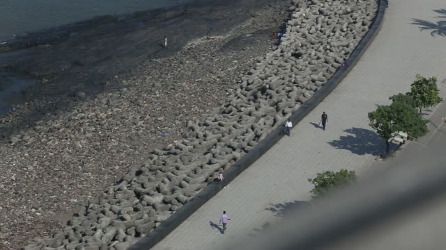 High angle view of traffic on road beside the promenade and pan High angle view of breakwater next to promenade High angle view of pedestrians...