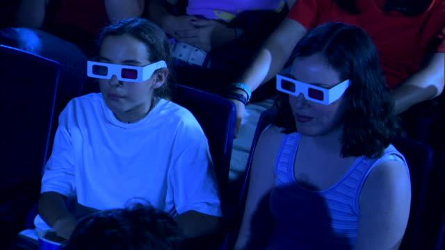 high angle view of two girls eating popcorn while watching a 3d movie. - biosalong bildbanksvideor och videomaterial från bakom kulisserna