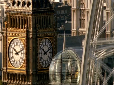 t/l mcu high angle view of two sides of big ben with pods from london eye ferris wheel passing right of frame - london eye stock-videos und b-roll-filmmaterial