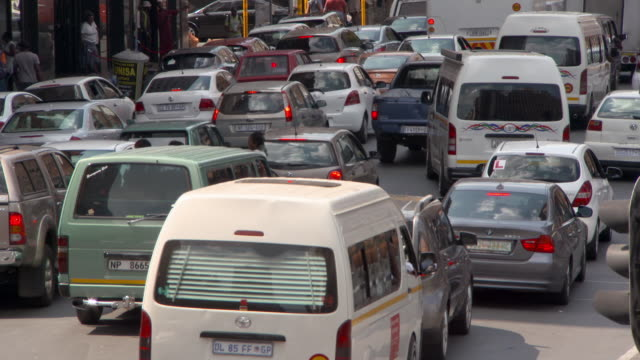 high angle view of vehicles on street with people in city during rush hour - johannesburg, south africa - dringlichkeit stock-videos und b-roll-filmmaterial