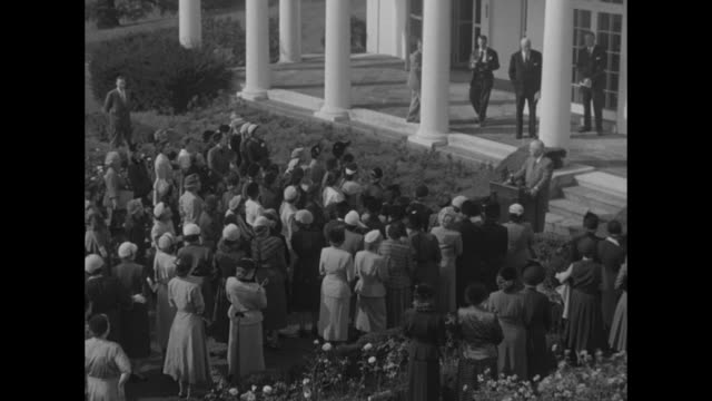 High angle view of well dressed women in Rose Garden of White House near Oval Office and West Wing Colonnade with President Harry Truman speaking...