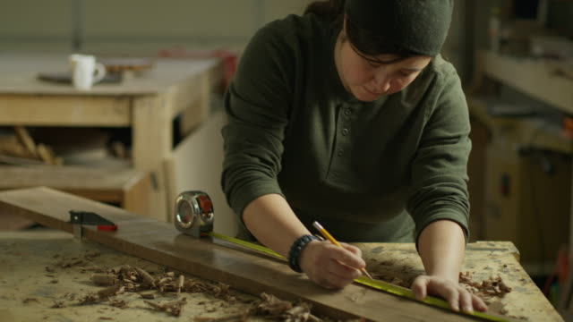 high angle view of woman measuring wood with tape measure in workshop / provo, utah, united states - provo stock videos & royalty-free footage