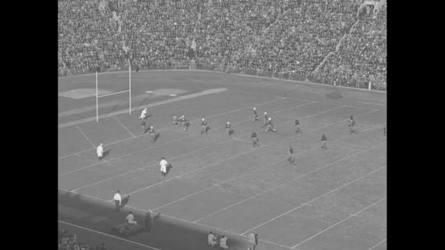 High angle view of Yale Bulldogs' kickoff to Princeton Tigers / Garry LeVan kicks near goalposts Yale's Jerry Roscoe receives running back to...