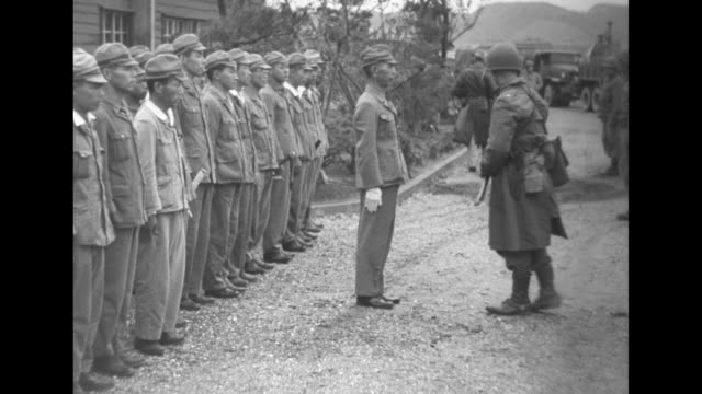 vídeos de stock, filmes e b-roll de high angle view of yokosuka / american soldiers receive surrendered swords and daggers from japanese troops / all stand at attention with a pan of... - prisoner