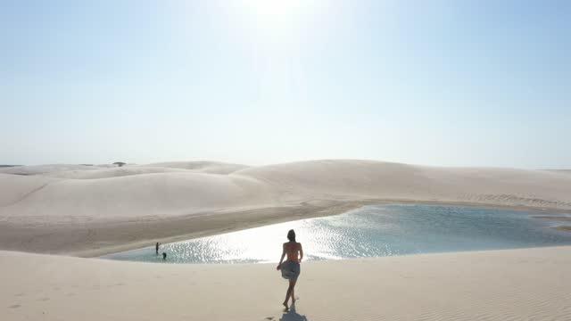 vídeos de stock, filmes e b-roll de visão de alto ângulo de jovem andando em dunas de areia em jericoacoara, ceará, brasil - horizonte