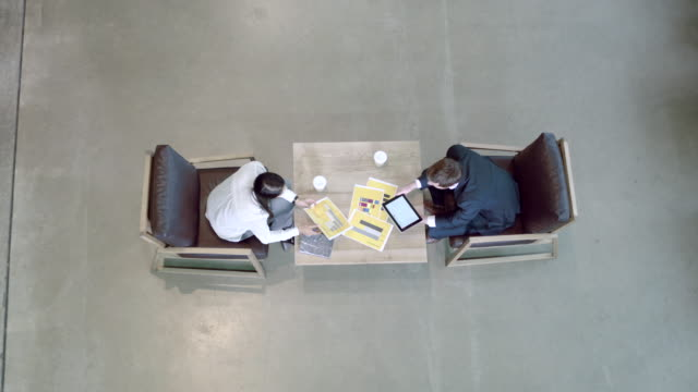high angle view on business meeting in office lobby - strategia di vendita video stock e b–roll