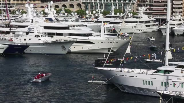 high angle view superyachts and other smaller luxury vessels sit moored in the harbor during the monaco yacht show in monaco, france, on thursday,... - モーターボート点の映像素材/bロール