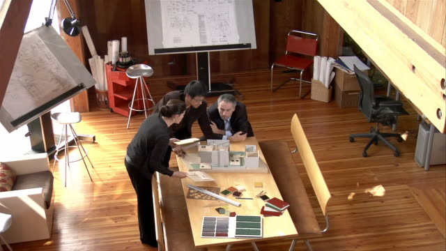 high angle view three businesspeople talking and looking at architectural model - 模型点の映像素材/bロール