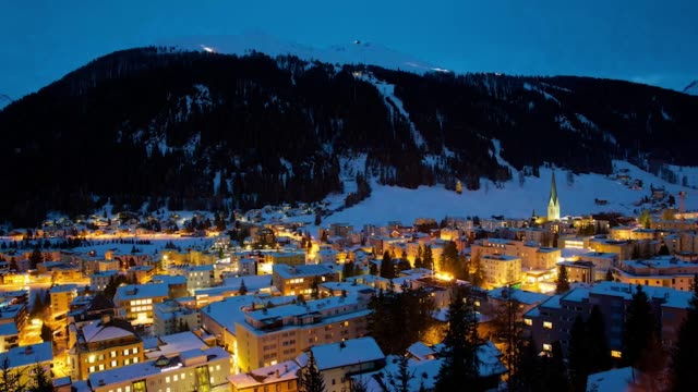 High angle view time lapse shows snowcovered buildings illuminated during sunset in the town of Davos the location for the World Economic Forum's...