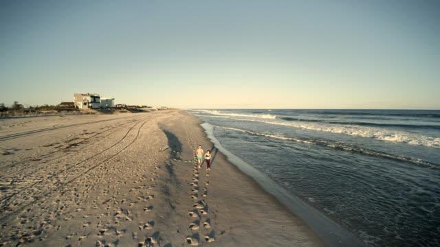 ビーチでジョギング男と 10 代の若い女の子に高角度のビュー。空中映像。 - ロングアイランド点の映像素材/bロール