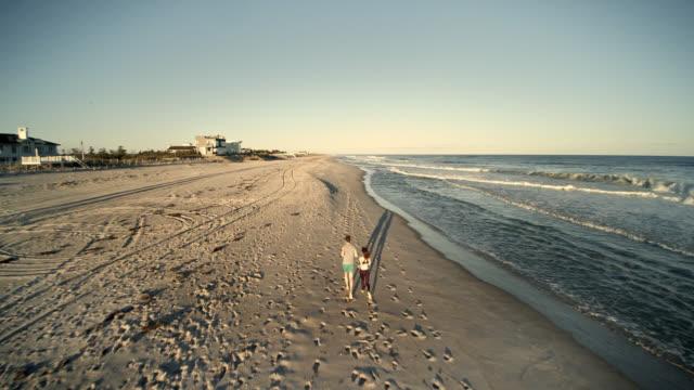 stockvideo's en b-roll-footage met hoge hoekmening aan jonge man en tiener meisje joggen op het strand. luchtfoto beeldmateriaal. - volgen activiteit