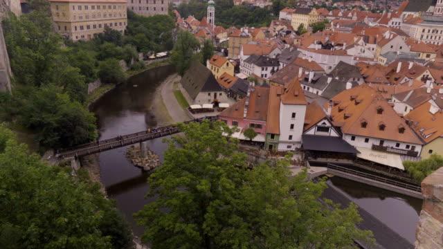 vídeos y material grabado en eventos de stock de vista de ángulo alto: el viajero camina sobre el puente de madera hacia la ciudad de cesky krumlov - cultura checa