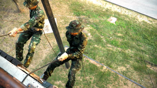 high angle view: two soldier training rappel with rope by back down. military man does hanging on climbing equipment - abseiling stock videos & royalty-free footage