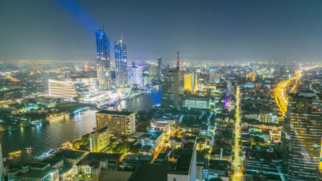 high angle view urban cityscape skyline with crowded tall buildings and river at night. - tall high stock videos and b-roll footage