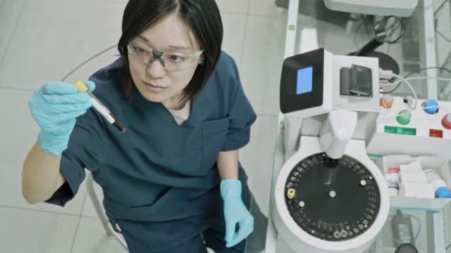 vídeos de stock, filmes e b-roll de vídeo da opinião do ângulo elevado do técnico fêmea asiático da patologia que trabalha no laboratório - no alto