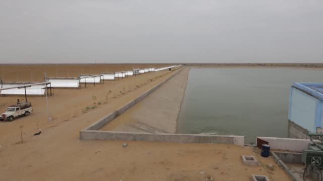 High angle view water is released into a reservoir beside parabolic troughs at the Godawari solarthermal power plant operated by Godawari Green...