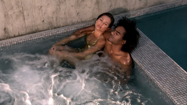 high angle view. young couple relaxing in hot tub. - haar nach hinten stock-videos und b-roll-filmmaterial