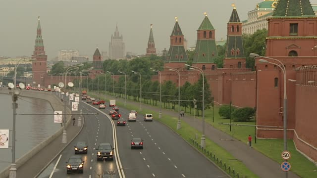 high angle views city traffic going up and down road outside walls of the moscow kremlin adjacent to the moscow river / wide shots red square and... - cattedrale video stock e b–roll