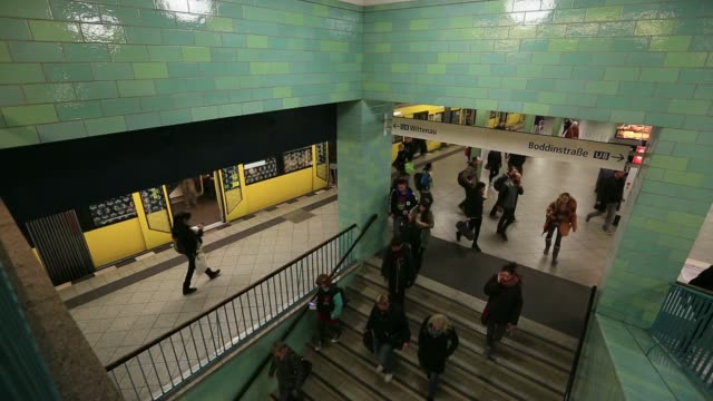 high angle views commuters walking from trains and up and down stairs to platform at alexanderplatz u bahn underground railway station in berlin... - u bahnsteig stock-videos und b-roll-filmmaterial