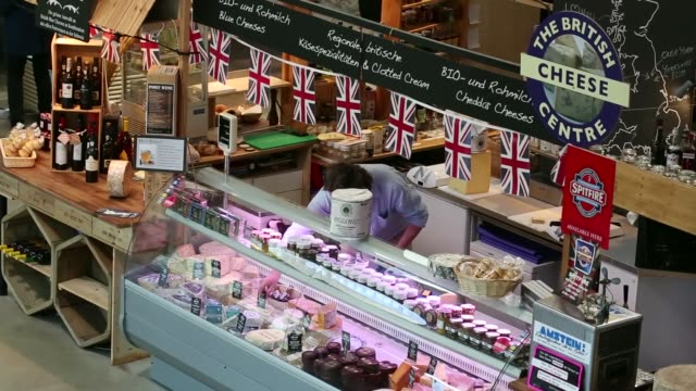 high angle views michael fontana-jones, owner of the british cheese centre, works at his stall selling british cheeses, at the viadukt indoor market... - display cabinet stock videos & royalty-free footage