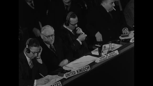 VS high angle views of Soviet foreign minister Andrey Vyshinsky reading a statement in Russian while seated next to United States' and United...