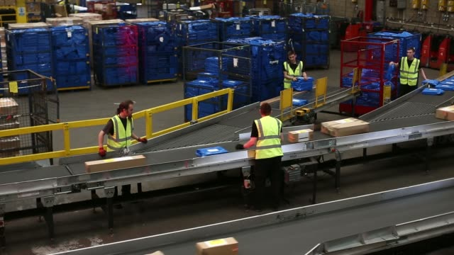 high angle views red lights illuminate packages as they pass through a scanning machine ahead of loading for delivery at uk mail group plcs letter... - post structure stock videos & royalty-free footage
