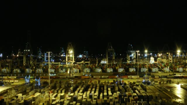 vídeos de stock, filmes e b-roll de high angle views shipping containers and gantry cranes stand illuminated at night in the port of rotterdam seen from the maersk mckinney moeller... - de perna aberta