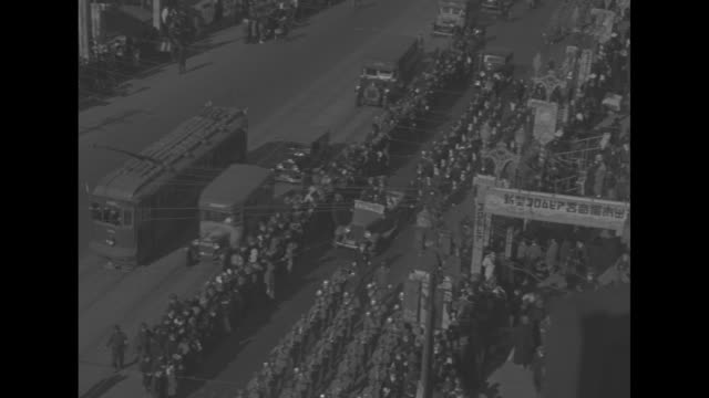 high angle vs at the side of a street with light traffic, hundreds of various marching bands are seen on right side of an avenue in tokyo; they march... - 日本の皇室点の映像素材/bロール