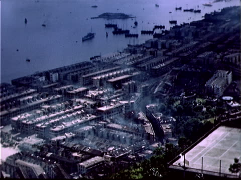 1939 High angle wide boats in harbor near dense industrial area/ Hong Kong