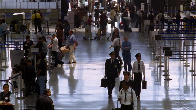 High angle wide shot airline pilots walking through terminal at LAX / passengers getting in line / Los Angeles