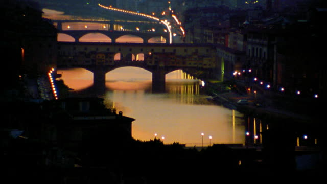high angle wide shot arno river and ponte vecchio bridge at dusk / florence, italy - ponte stock-videos und b-roll-filmmaterial