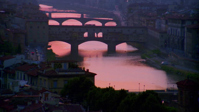 high angle wide shot arno river and ponte vecchio bridge at dusk / florence, italy - florence italy stock videos & royalty-free footage