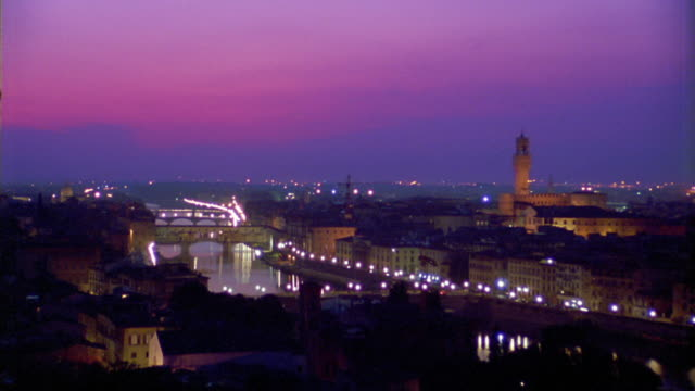 high angle wide shot arno river with ponte vecchio and buildings at dusk / florence, italy - ponte stock-videos und b-roll-filmmaterial