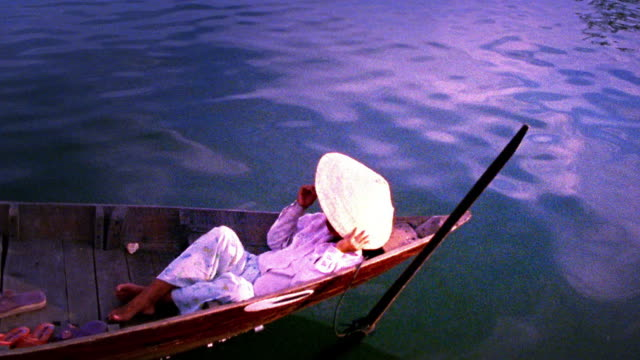 high angle wide shot asian woman lying in riverboat with asian style straw hat over face / china (flash frames) - straw hat stock videos & royalty-free footage