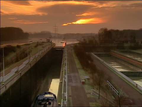 high angle wide shot barge pulling into lock at sunrise/ germany - anno 2002 video stock e b–roll